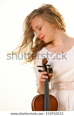 Portrait of blonde girl music lover on beach with a violin. Love of music concept.