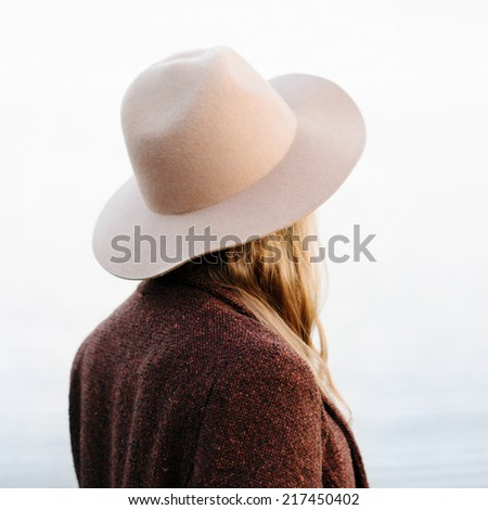Portrait of blonde girl standing back to camera outside. Wearing hat and jacket. Outside - stock photo