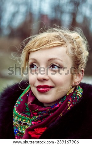 Portrait of blonde girl with red lips. Cold winter weather. Romantic smile.