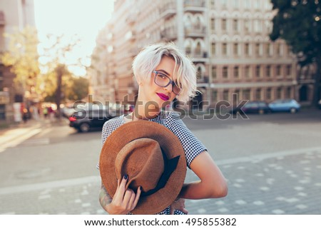 Portrait of  blonde girl with short hair looking to the camera on the street on sunset background. She wears gray checkered  dress, glasses. She holds hat in hand.