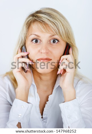 portrait of blonde girl with two mobile phones - stock photo
