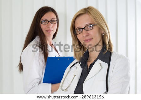 Portrait of Blonde Hair Female Doctor With Glasses and Her Medical Colleague With Clipboard in Background Smiling and Looking at Camera, Half-Length Shot - stock photo