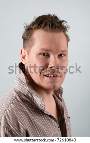 portrait of blonde man in shirt posing on gray - stock photo
