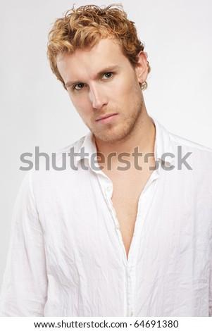 portrait of blonde man in white shirt posing on gray - stock photo