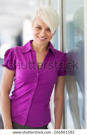Portrait of blonde smiling woman standing next to a glass wall - stock photo