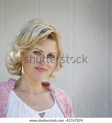 Portrait of blonde woman in natural light in front of white wall