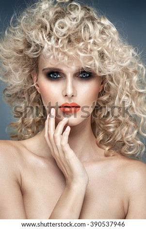 Portrait of blonde woman with curly blond hair and perfect make-up - stock photo