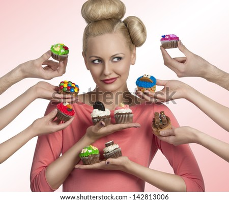 portrait of blonde woman with funny make-up and hair-style. Some hands tendering colorful cupcakes near her face