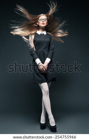 portrait of blonde young beautiful posing woman wearing eyeglasses and black dress with white collar. Her long hair fluttering in wind and legs crossed. - stock photo