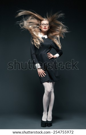 portrait of blonde young beautiful posing woman wearing eyeglasses and black dress with white collar. Her long hair waving. - stock photo