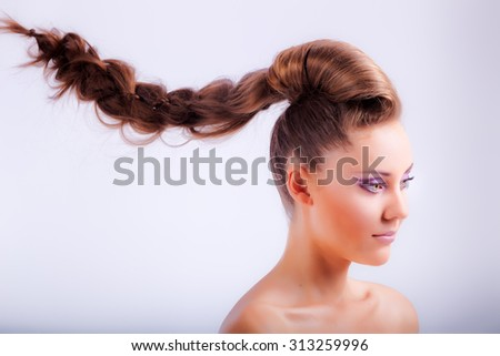 portrait of blonde young girl in elegant whimsical coiffure hanging in air with naked shoulders - stock photo