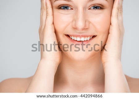 Portrait of blonde young pretty girl, smiling, looking at camera, hands on cheeks, over white background.