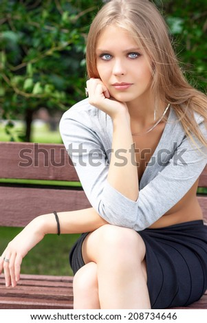 Portrait of blonde young woman sitting on the bench in summer park - stock photo