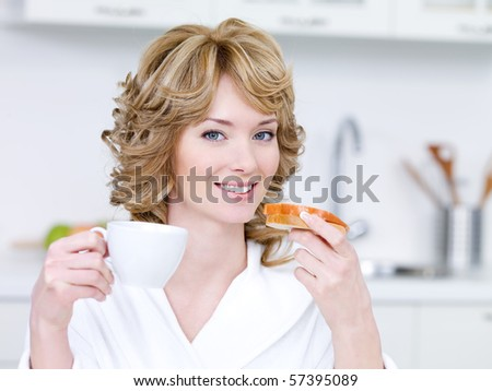 Portrait of blonde young woman with happy smile having a breakfast in the kitchen - stock photo
