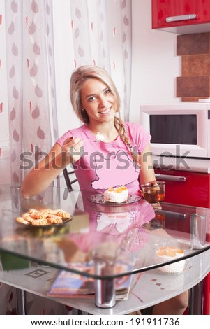 Portrait of blondy sweet girl hand holding a spoon with cake  Blond woman in pink shirt sitting in the kitchen on glass transparent table - stock photo