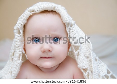 portrait of blue-eyed baby in white blanket