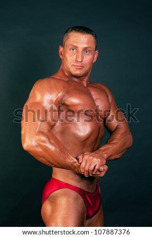 Portrait of bodybuilder posing on dark background. - stock photo