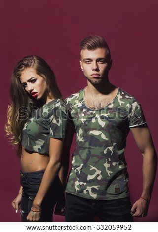 Portrait of bold cool sexual attractive charming fearless young couple models dressed in fashion camouflage style t-shirts looking straight posing on purple background studio, vertical picture - stock photo