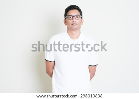 Portrait of bored Indian guy with serious face expression. Asian man standing on plain background with shadow and copy space. Handsome male model. - stock photo