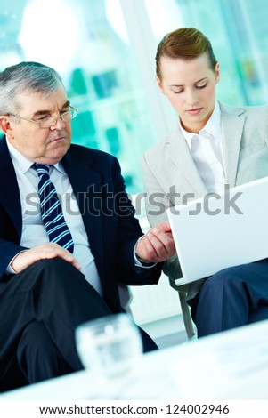 Portrait of boss and employee working with laptop in office - stock photo