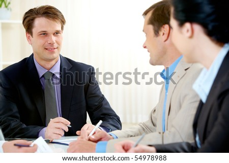 Portrait of boss explaining work to his colleagues - stock photo