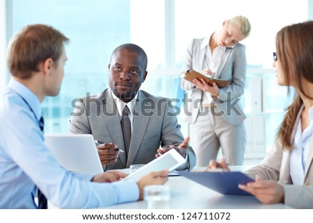 Portrait of boss looking at his employee sitting near by - stock photo