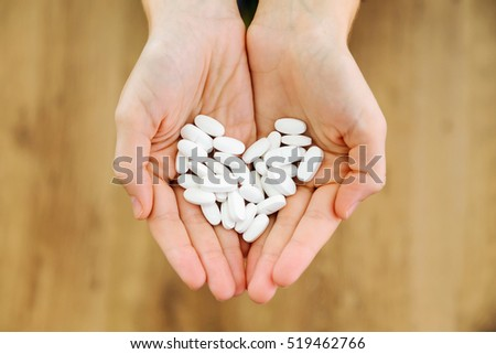 Portrait of both hands holding bunch of pills. Overdose or abuse concept.