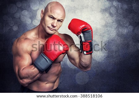Portrait of boxer with red gloves against black wall - stock photo