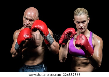 Portrait of boxers with gloves against black background - stock photo