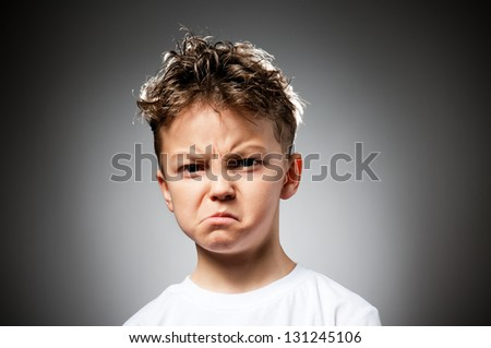Portrait of boy anger on gray background - stock photo