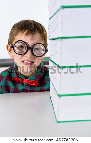 Portrait of boy by stacked books on table in classroom - stock photo