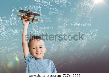 Portrait of boy holding wooden toy airplane against blue sky