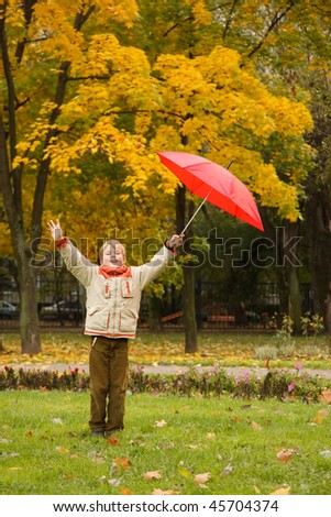Portrait of boy in autumn park. Hands are lifted, in one red umbrella.
