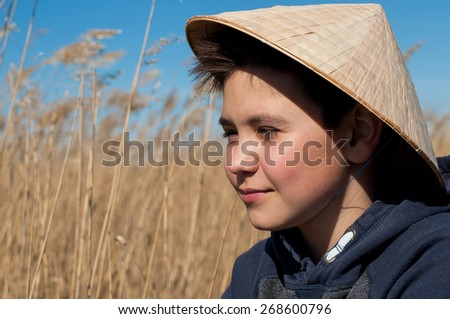 Portrait of boy in chinese hat - stock photo