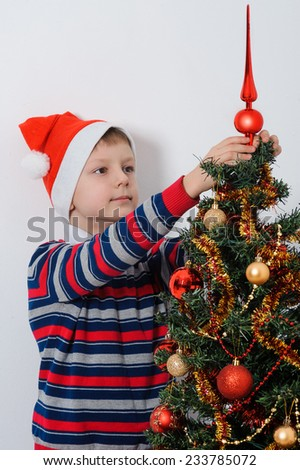 Portrait of boy in Santa cap decorating Christmas tree with baubles - stock photo