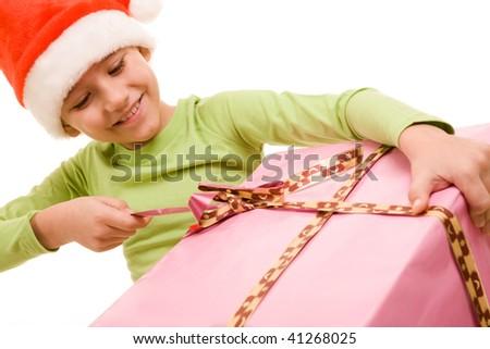 Portrait of boy in Santa cap unwrapping ribbon of smart present - stock photo
