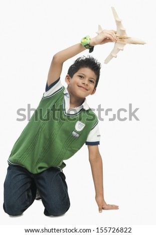 Portrait of boy playing with toy airplane