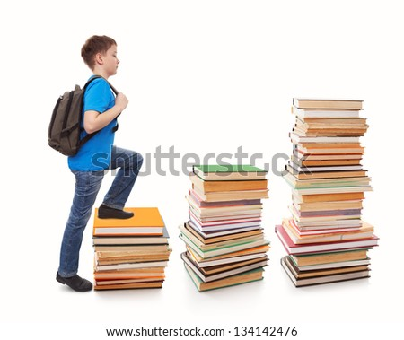Portrait of boy walking from top to top of book piles - stock photo