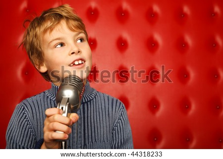 Portrait of boy with microphone on rack against red wall looking aside. Horizontal format. - stock photo