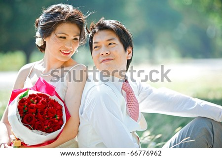 portrait of bride and groom making eye contact with rose bouquet