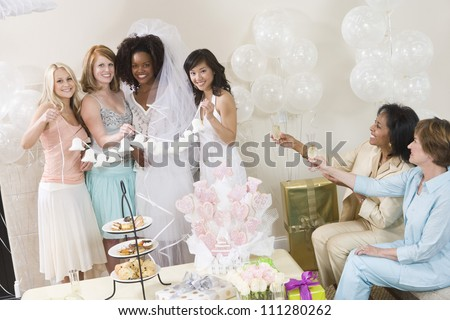 Portrait of bride and her friends holding wedding bells with women toasting champagne at party