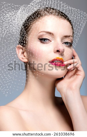 Portrait of Bride. Beautiful woman in veil touching her face. Vertical Portrait. - stock photo