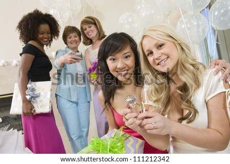 Portrait of bride sitting with her friend showing big engagement ring at  party - stock photo