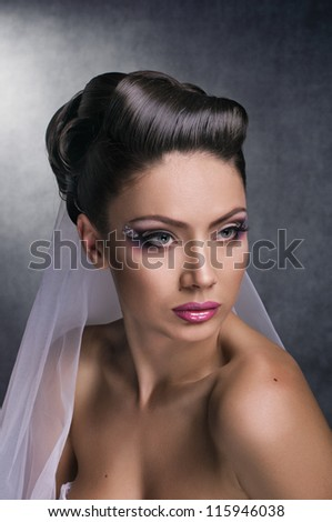 portrait of bride with coiffure and make up on grey