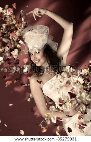 portrait of bride with rose petals on the background of fire