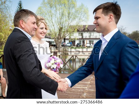Portrait of brides father shaking hands with groom at wedding ceremony - stock photo