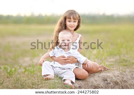 portrait of Brother and sister in summer nature  - stock photo