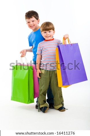 Portrait of brothers holding shopping bags and looking at camera happily - stock photo