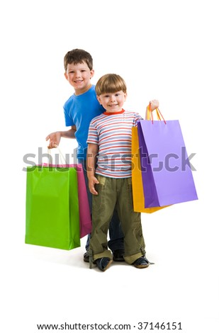 Portrait of brothers holding shopping bags and looking at camera happily
