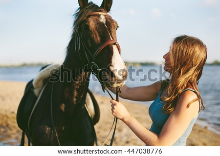 Portrait of Brown horse with brown hair woman outdoor. Enjoy of communicating with animals, freedom in nature - stock photo